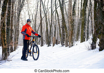 Mountain Biker with Bike on the Snowy Trail in Beautiful Winter Forest