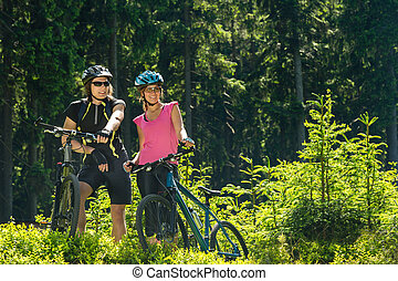 Mountain bikers resting in forest - Mountain bikers standing...