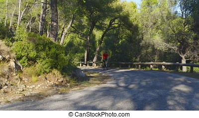 Mountain Biking - Athletic guy on a mountain bike who is driving uphill on a beautiful secondary road - ProRes