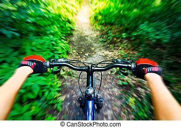Mountain biking down hill. View from biker.