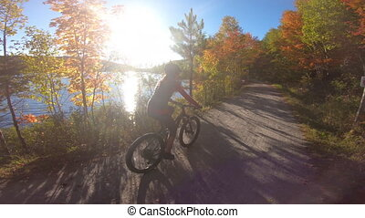Mountain biking in autumn. Mountain biker riding MTB bicycle on forest gravel in fall foliage with colorful leaves. Woman living healthy lifestyle. Petit train du nord, Mont Tremblant, Quebec, Canada