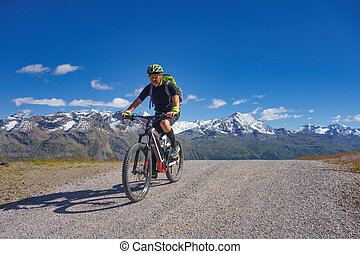 Mountain biking in the high mountains on a dirt road