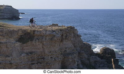 Mountain biking on cliff by sea