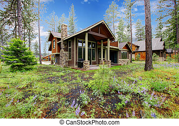 Mountain cabin home exterior with forest and flowers.