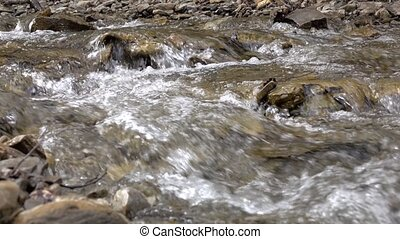 Mountain calm stream among stone banks with clear spring water