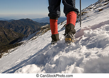 Mountain climber foot walk on snow slap.