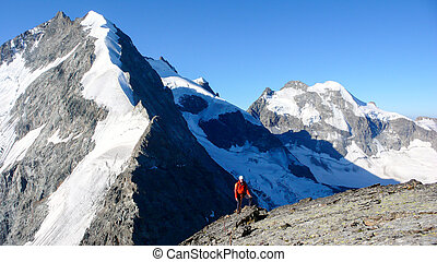 mountain climber on a high alpine summit in the Swiss Alps