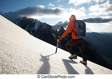 Mountain climber - Lone male mountain climber climbing a...