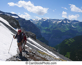 mountain climbers heading to the foot of Eiger and Moench mountain peaks in the Swiss Alps near Grindelwald
