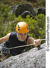 Mountain climbing - Man climbing a mountain with a protetive...
