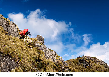 Mountain climbing of man back heavy red backpack walking.