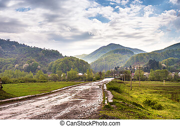 Road and village in green mountain valley