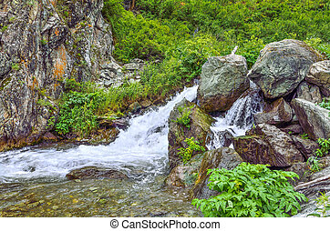 Mountain creek with waterfalls under cliff among boulders in Altai mountains