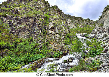 Mountain creek with waterfalls under cliffs among boulders in Altai mountains