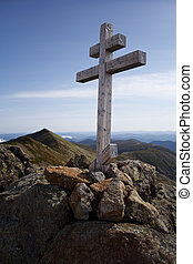 mountain cross with bit mountains in the background
