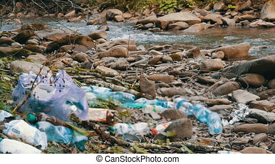 Mountain fast clean stream, on a rocky shore, which has garbage, plastic bottles, bags. The human factor in environmental pollution. Special garbage defocus
