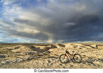 fat bike in badlands with storm clouds