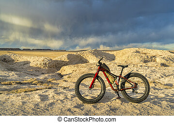 fat bike in badlands with storm clouds - mountain fat bike ...