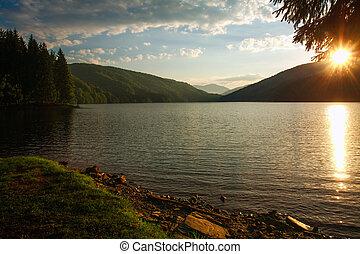 Mountain forest lake on background dramatic sunrise sky