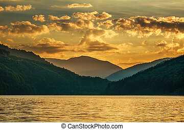 Mountain forest lake on background dramatic sunset sky