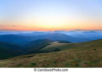Autumn sunrise mountain view with haze, forest and sun on sky (Carpathian, Ukraine)