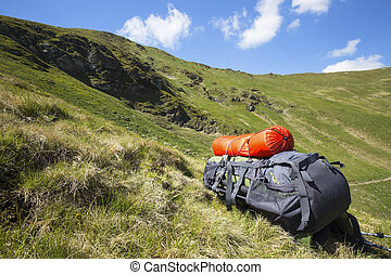 Mountain hiking backpack equipment on the grass with mountain landscape background