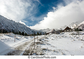 Mountain Hut with Snow between High Mountains in Winter
