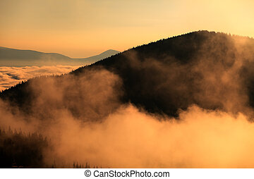 mountain in clouds and hills in fog