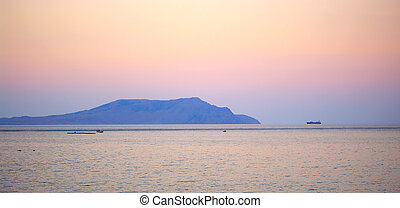Mountain in sea at sunset