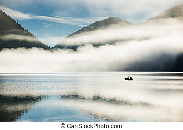 mountain lake at morning with a lonely fisherboat in autrian alps