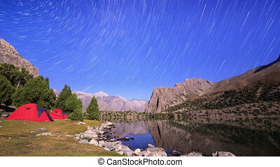 Mountain lake at night. Traces of stars similar to metory. Time Lapse. Pamir, Tajikistan
