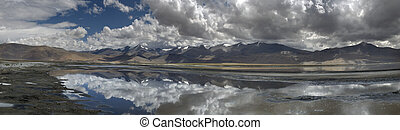 Mountain lake on a cloudy day: heavy clouds reflected in the mirror surface of the water, panorama, the Himalayas.