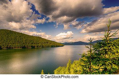 mountain lake under cloudy sky
