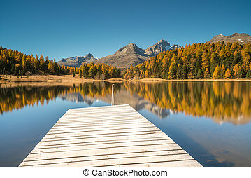 mountain lake with a wooden pier and reflections of fall colors