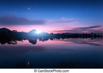 Mountain lake with moonrise at night. Night landscape
