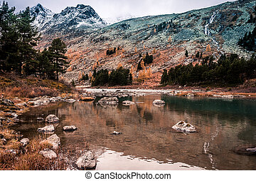 Mountain lake with reflection in the mirrored surface of the rocks in cloudy rainy weather in the fall. The beauty of this mountainous country, nature in autumn.