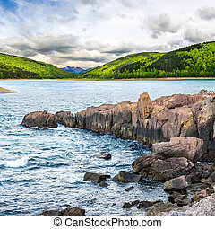 mountain lake with rocky shore at sunrise - composite image...