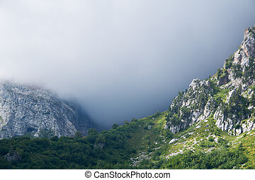 mountain landscape - a pass lit by the sun and a gloomy cloud behind it