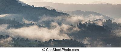 Mountain landscape after storm. Clouds of fog. Misty village