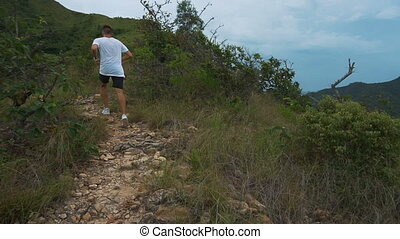 Mountain landscape caucasian running man jogging in the morning slow motion