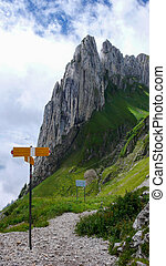 mountain landscape in the Toggenburg region of Switzerland with jagged mountain peaks and a yellow hiking trail sign