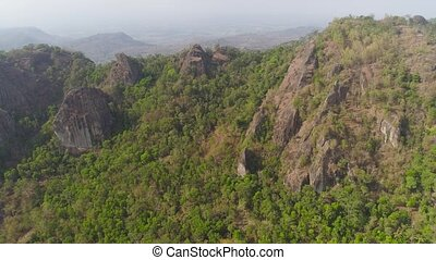 mountain landscape high cliffs mountains covered with green tropical forest. aerial view mountain forest with large trees and green grass. tropical landscape in asia Jawa, Indonesia