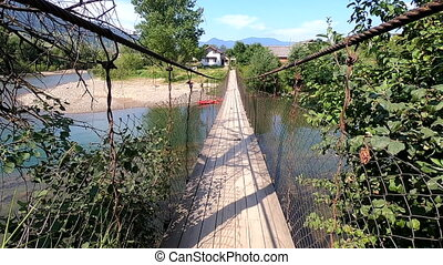 Summer scenery from mountain landscape, suspension bridge flowing river. Nature, natural background, environmental protection backdrop. Concept eco, ecotourism, environmentally friendly. Entertainment