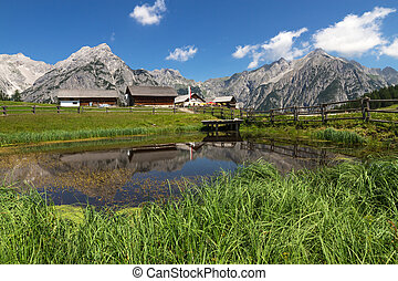 Mountain Landscape with with a lake in the foreground. Austria, Tirol, Walderalm.