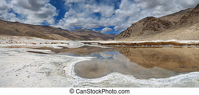 Mountain mineralized lake, wavy line of salt beach, in the water reflect the mountains, panorama, the Himalayas.