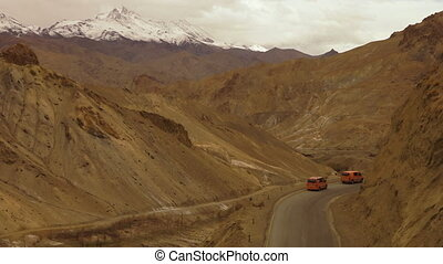 Medium, high-angle still shot of tour vehicles moving down a well tarmac ked mountain pass. In the horizon is a snowing Indian Himalayan mountain peak.
