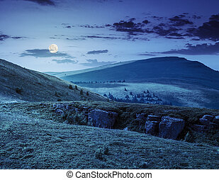 mountain peak behind hillside with boulders at night - view...