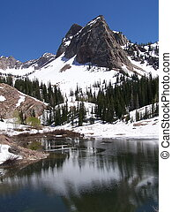 This mountain peak still covered in snow reflects off the mountain lake in the early spring thaw.