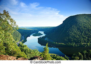 Mountain peak view with blue sky, river and trees from ...