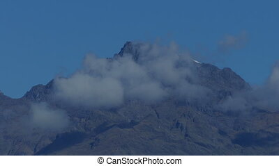 Mountain Peak With Clouds Moving Past - Clouds forming near...